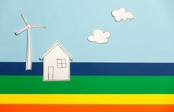 家庭模型和风车在五颜六色的背景 库存照片