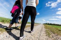 家庭步行在乡下在一个晴天 腿透视 库存照片