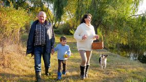 家庭步行,有孙子的愉快的祖父母与狗一起审阅渔的森林湖周末 影视素材