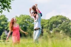 家庭步行-生在他的肩膀的运载的孩子 免版税库存图片