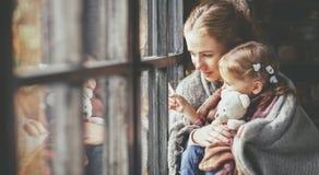 家庭母亲和儿童女儿看多雨秋天的窗口 免版税库存照片