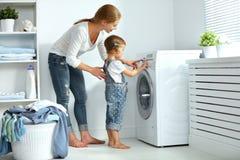家庭母亲和儿童小帮手在washi附近的洗衣房 免版税图库摄影