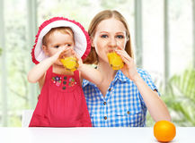 家庭母亲和喝在总和的小女儿橙汁 免版税图库摄影
