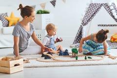 家庭母亲和孩子播放在游戏室的一条玩具铁路 免版税图库摄影