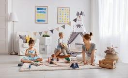 家庭母亲和孩子播放在游戏室的一条玩具铁路 免版税库存图片
