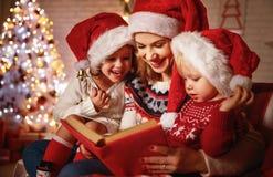 家庭母亲和孩子读了一本书在圣诞节靠近firep 免版税库存照片