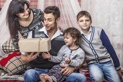 家庭母亲父亲和孩子互相给在您的礼物 免版税库存图片