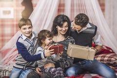 家庭母亲父亲和孩子互相给在您的礼物 免版税图库摄影