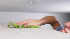 家庭清洁概念 一个人在他的房子里抹从一个高内阁的尘土 影视素材