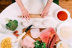 家庭烹饪细节-妇女在准备面团的厨房里 库存图片