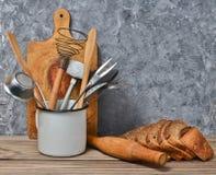 家庭烹饪,面包店 木板,厨房工具,在一张桌上的黑麦面包在一个灰色混凝土墙的背景 免版税图库摄影