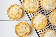 家庭焙制传统英国圣诞节酥皮点心的点心与苹果计算机填装在冷却的机架的葡萄干坚果的肉馅饼 库存图片