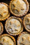 家庭焙制传统英国圣诞节酥皮点心的点心与苹果计算机填装酥皮糕点搽粉的顶视图的葡萄干坚果的肉馅饼 免版税图库摄影