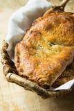 家庭焙制的意大利酥皮点心Calzone用填装在白色亚麻布餐巾的柳条筐的甜苹果饼葡萄干桂香 木表 库存照片