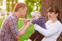 家庭父母身分概念-愉快的母亲使用在夏天的父亲和小女孩停放 免版税库存照片