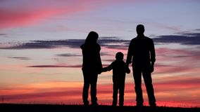 家庭现出轮廓画象在日落、父母和儿童举行手,战无不胜 股票录像