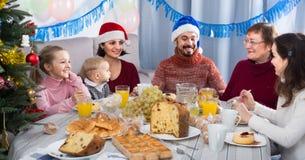 家庭生气蓬勃谈话在圣诞晚餐期间 库存图片