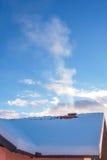 家庭用与发烟的雪盖的房子屋顶 库存图片