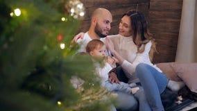家庭田园诗、年轻父母和孩子在家坐接近xmas树的圣诞节早晨在屋子里 股票视频