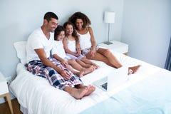 家庭画象使用一起膝上型计算机的在床上 图库摄影
