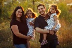 家庭画象四在与小女孩的秋天森林公园孪生 愉快的人民,微笑和亲吻 温暖的晚上阳光 免版税库存图片