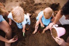 家庭的中央部位有使用在海滩的小孩孩子的在度假夏天休假 免版税库存照片