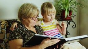 家庭的历史 有她的孙女叶子的祖母通过家庭照片册页 股票视频
