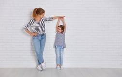 家庭的概念 母亲测量孩子成长对daught 免版税图库摄影