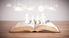 家庭的纸板形象在被打开的书 免版税库存图片