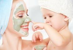 家庭秀丽治疗在卫生间里 母亲和女儿女婴做面孔皮肤的一个面具