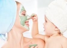 家庭秀丽治疗在卫生间里 母亲和女儿女婴做面孔皮肤的面具 免版税库存照片