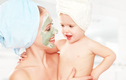 家庭秀丽治疗在卫生间里 母亲和女儿女婴做面孔皮肤的面具 免版税库存图片
