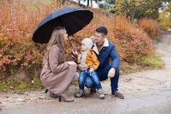 家庭秋天在雨伞的公园 免版税库存照片