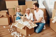 家庭移动 有箱子的愉快的人在新的公寓 免版税库存照片
