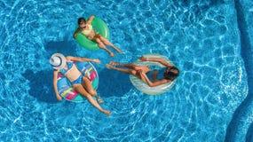 家庭空中顶视图在从上面游泳池的,愉快的母亲和孩子在可膨胀的圆环油炸圈饼游泳并且获得乐趣在水中 免版税库存图片