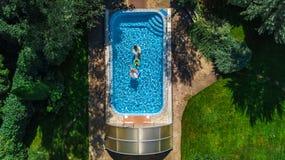 家庭空中顶视图在从上面游泳池的,愉快的母亲和孩子在可膨胀的圆环油炸圈饼游泳并且获得乐趣在水中 库存照片
