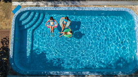 家庭空中顶视图在从上面游泳池的,母亲和孩子在水中游泳并且获得乐趣家庭度假 免版税库存图片