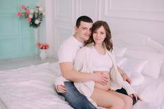 家庭等待的婴孩` s诞生 一名孕妇和她的丈夫佩带的白色衣物 图库摄影