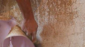 家庭维修服务 男性手剥落从墙壁的桃红色老墙纸有特别小铲关闭的 股票视频