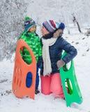家庭获得与雪撬的乐趣在冬天公园 免版税图库摄影