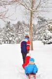 家庭获得与雪橇的乐趣在白色雪 库存图片