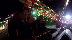 家庭获得乐趣在一个转动的轮子在游乐园、年轻父母和小孩兴奋,色夜 股票视频
