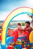 家庭获得乐趣在与幻灯片和许多的inlatable水池五颜六色的球 免版税库存图片