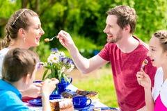 家庭获得乐趣在咖啡时间在庭院 免版税库存图片