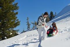 家庭获得在新鲜的雪的乐趣冬天假期 图库摄影