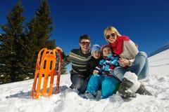 家庭获得在新鲜的雪的乐趣在冬天 图库摄影