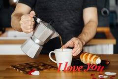 家庭衣裳的人倒热的咖啡入有词的我爱你一个杯子从在桌上的红色纸与蛋糕,反对bac 图库摄影
