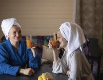 家庭衣裳的妇女喝汁液 库存照片
