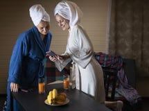 家庭衣裳的妇女喝汁液 图库摄影
