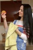 家庭衣裳的主妇浅黑肤色的男人抹苹果绿的毛巾 免版税库存图片